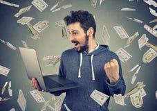 Lyckad ung man som använder bärbara datorn som bygger online-pengar för affärsförtjänst royaltyfria foton