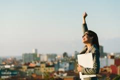 Lyckad ung stadsaffärskvinna som lyfter armen Arkivfoton