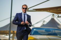 Lyckad yang affärsman i gul cabriobil royaltyfri fotografi