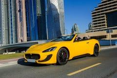 Lyckad yang affärsman i gul cabriobil arkivbilder