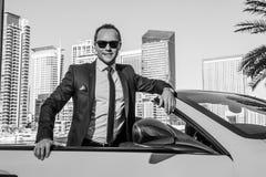 Lyckad yang affärsman i gul cabriobil arkivbild