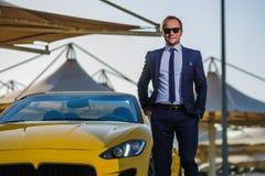 Lyckad yang affärsman i gul cabriobil royaltyfri bild