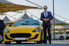 Lyckad yang affärsman i gul cabriobil royaltyfri foto