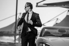 Lyckad yang affärsman i gul cabriobil arkivfoton