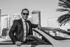 Lyckad yang affärsman i gul cabriobil royaltyfria foton