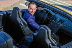 Lyckad yang affärsman i gul cabriobil royaltyfria bilder