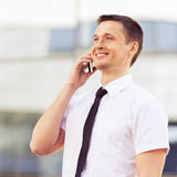 Lyckade män som kallar på mobiltelefonen Arkivbilder