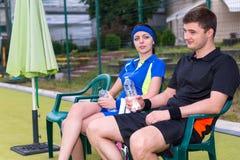 Lyckade par av tennisspelare som har en vila med flaskan av Arkivfoton