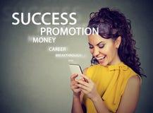 Lyckade unga läs- goda nyheter för affärskvinna på hennes smarta telefon Royaltyfri Bild