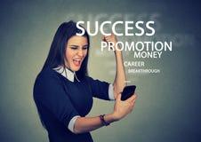 Lyckade unga läs- goda nyheter för affärskvinna på hennes smarta telefon Royaltyfria Bilder