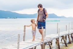 Lyckafader och son på pir på den soliga dagen under solljus arkivbilder