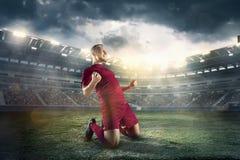 Lyckafotbollsspelare efter mål på fältet av stadion arkivfoto