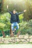 Lyckaframgång av en ung man utomhus Hoppa för glädje Royaltyfri Fotografi