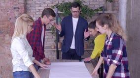Lyckat affärslag i modernt kontor, ung mentorman med kollegor som arbetar på utvecklingsprojekt av nytt arkivfilmer