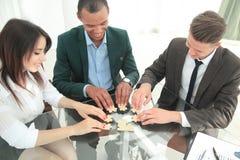 Lyckat affärslag som viker styckena av pusselsammanträdet bak ett skrivbord royaltyfri bild