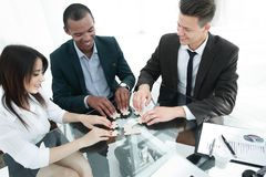Lyckat affärslag som viker styckena av pusselsammanträdet bak ett skrivbord arkivfoton