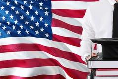 Lyckat amerikanskt studentutbildningsbegrepp Hållande böcker och avläggande av examenlocket över Amerikas förenta stater sjunker  royaltyfri foto