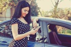 Lyckat anseende för ung kvinna av hennes bil som smsar på mobiltelefonen royaltyfri foto
