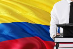 Lyckat colombianskt studentutbildningsbegrepp Hållande böcker och avläggande av examenlock över Colombia flaggabakgrund royaltyfri bild