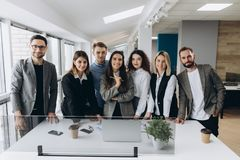 Lyckat företag med lyckliga arbetare i modernt kontor arkivbild