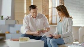 Lyckat gift par som räknar kontant hemmastatt, budget- pengar för familj, besparingar arkivfoto