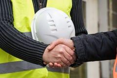 Lyckat handskakningavtal på konstruktionsplats Arkivbild