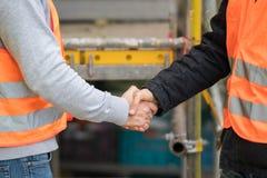 Lyckat handskakningavtal på konstruktionsplats Fotografering för Bildbyråer