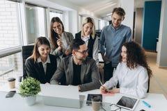 Lyckat lag Grupp av ungt aff?rsfolk som tillsammans arbetar och meddelar i id?rikt kontor arkivbilder