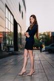 Lyckat le för affärsman som står på bakgrunden av byggnader och innehavet en minnestavladator Arbete för stadsaffärskvinna Royaltyfria Bilder