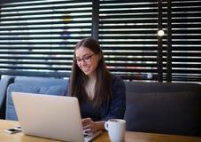 Lyckat on-line märkes- arbete för ung kvinna på bärbar datordatoren i coffee shopinre arkivbild