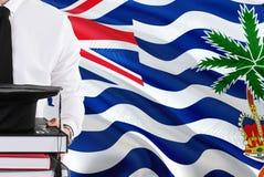 Lyckat studentutbildningsbegrepp Hållande böcker och avläggande av examenlock över bakgrund för flagga för brittiskt Indiska ocea royaltyfri bild