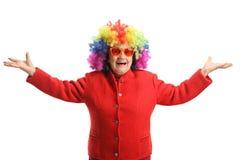 Lycklig äldre dam med ett rött lag och en färgrik peruk arkivbilder