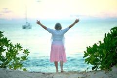 Lycklig äldre kvinna på stranden arkivbild