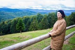 Lycklig äldre kvinna som överst står av kullen och tycker om bergsikt fotografering för bildbyråer