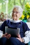 Lycklig äldre kvinna som använder en minnestavla som ser kameran och skratta Royaltyfri Bild