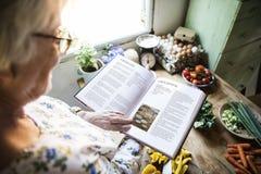Lycklig äldre kvinna som läser en kokbok arkivbilder