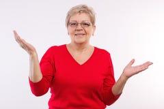 Lycklig äldre kvinna som rycker på axlarna skuldror och upp kastar hennes händer, sinnesrörelser i gamling Fotografering för Bildbyråer
