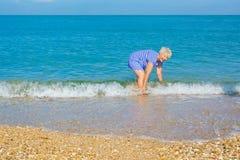 Lycklig äldre kvinna som tycker om på stranden Royaltyfria Bilder