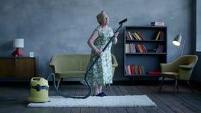 Lycklig äldre kvinnadans med en dammsugare, hem- gyckel stock video