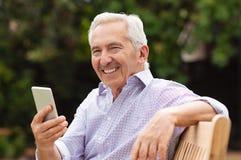 Lycklig äldre man som använder smartphonen royaltyfria bilder