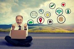 Lycklig äldre man som arbetar på datoren genom att använda social massmediaapplikation arkivbilder
