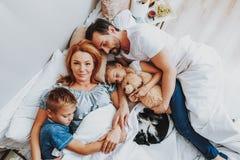 Lycklig älska familj som tillsammans sover i säng arkivbild