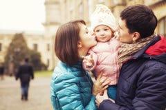 Lycklig älska family& x28; moder, fader och liten dotterkid& x29; outd arkivfoto