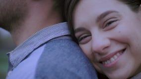 Lycklig älska parhipster som ler och kramar sig som har utomhus gyckel Flickan är på baksidan av en ung grabb arkivfilmer