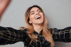 Lycklig älskvärd flickadanandeselfie med mobiltelefonen fotografering för bildbyråer