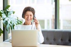 Lycklig åldrig kvinna i hörlurar med mikrofon och bärbar dator på tabellen royaltyfria foton