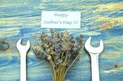Lycklig önska för faderdag, grupp av ursnygga lavendelblommor och skruvnycklar Arkivfoto