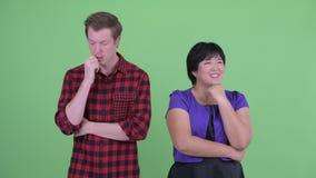 Lycklig överviktig asiatisk kvinna med den stressade skandinaviska hipstermannen som tillsammans tänker arkivfilmer