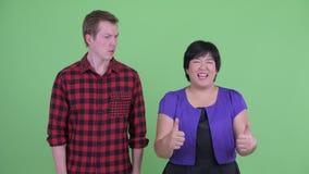 Lycklig överviktig asiatisk kvinna som ger upp tummar med den skandinaviska hipstermannen som ser förvirrad stock video