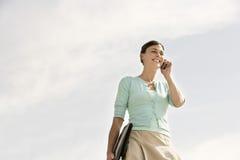 Lycklig affärskvinna Communicating On Cellphone mot molnig Sk royaltyfri foto